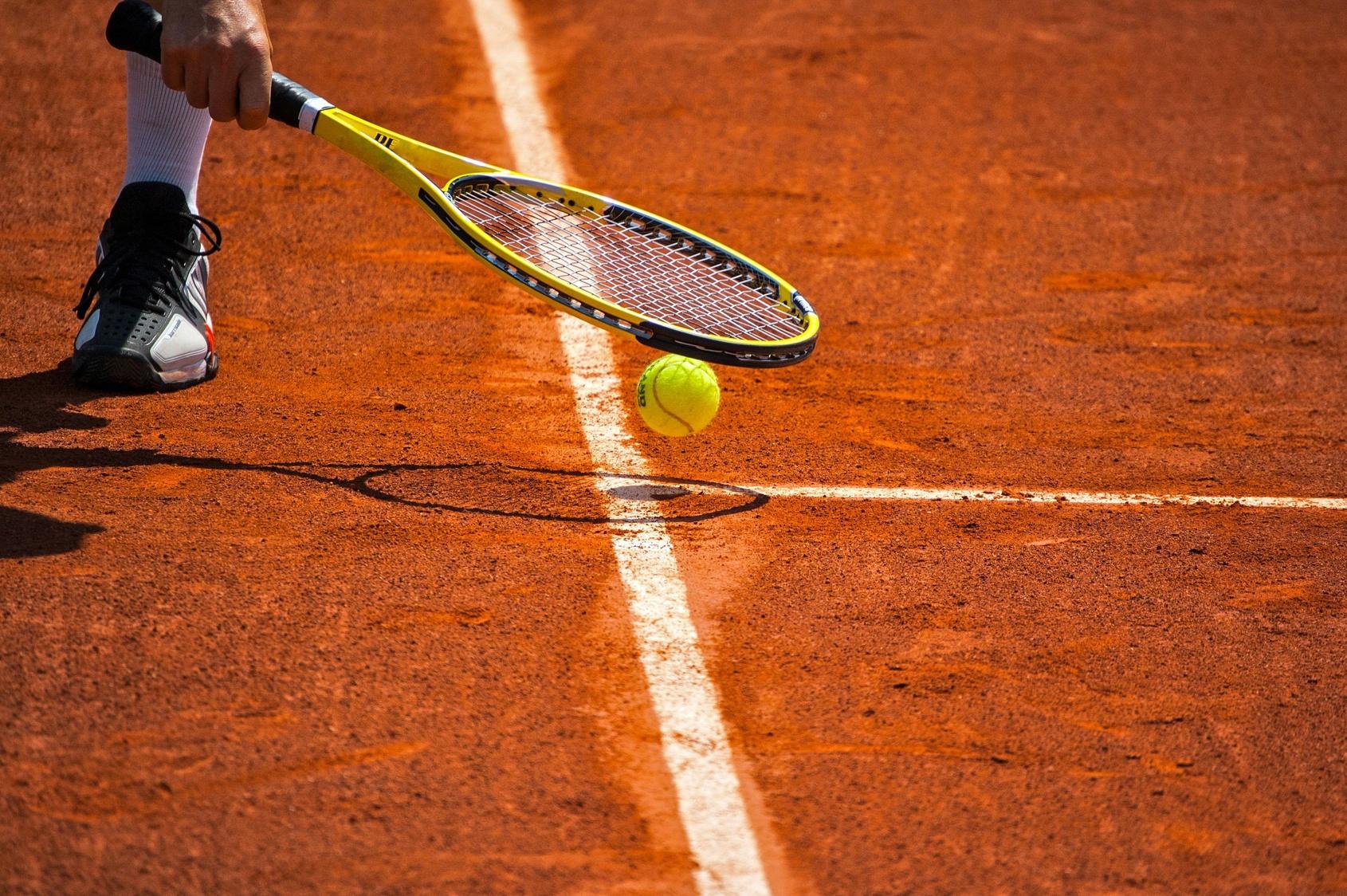 Terrain de tennis, raquette et balle jaune